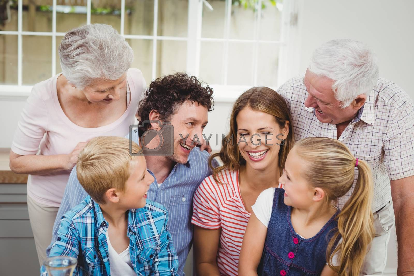 Cheerful multi-generation family against window at home