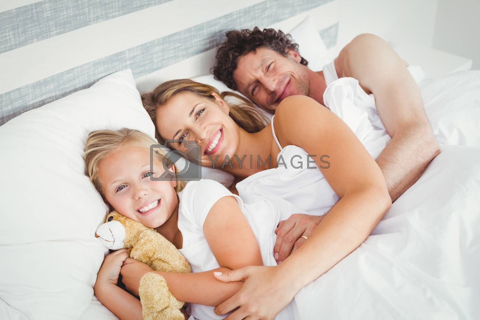 High angle view of smiling family relaxing on bed at home