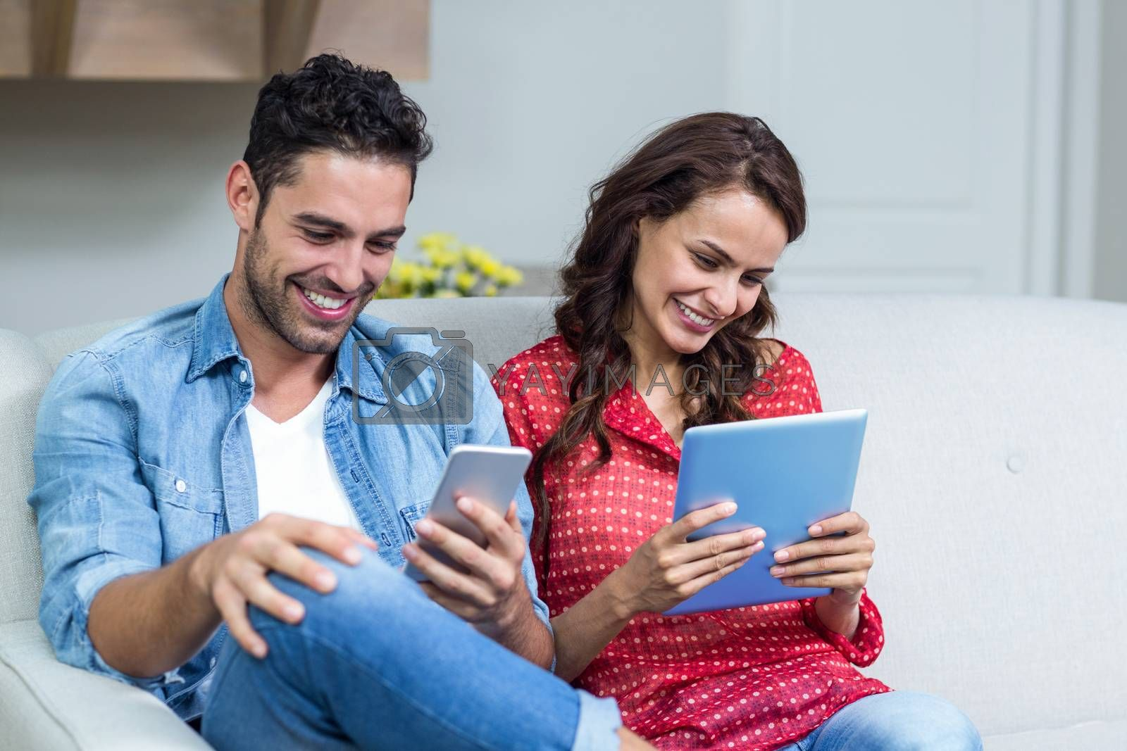 Smiling couple using technology at home
