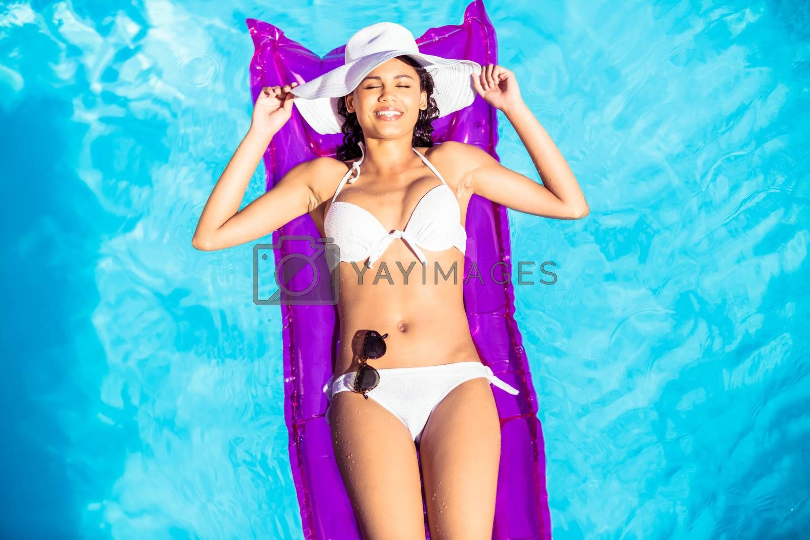 Woman in white bikini lying on air bed with her eyes closed