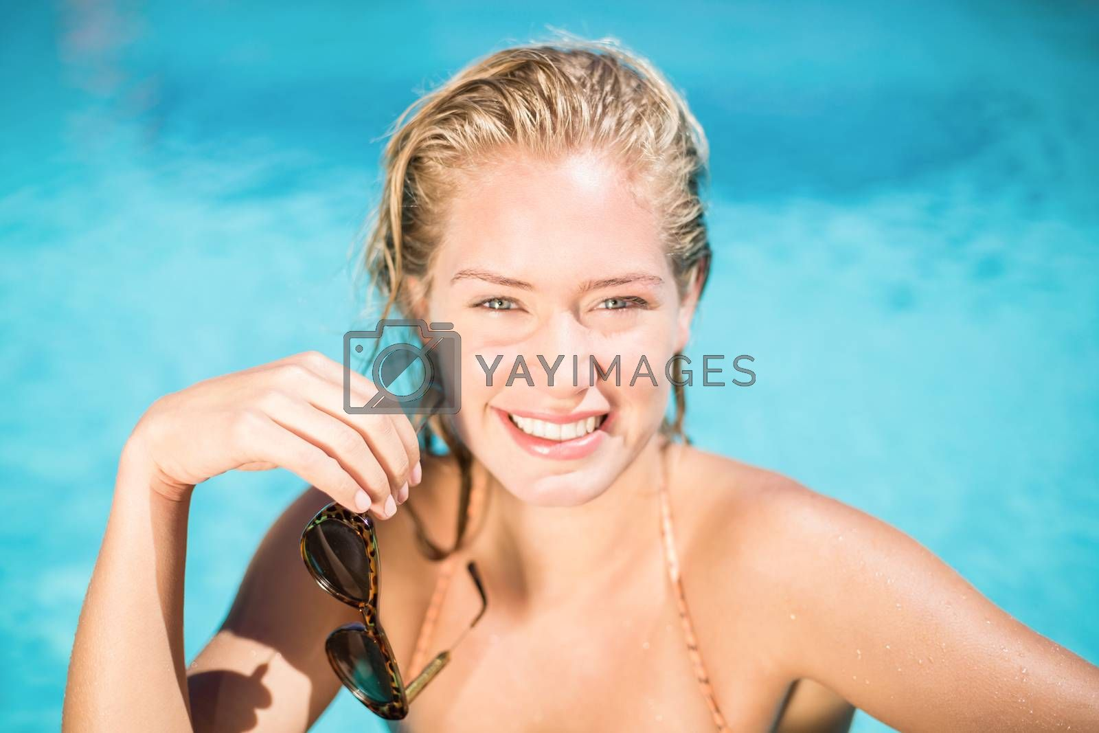 Portrait of beautiful woman leaning on poolside on a sunny day