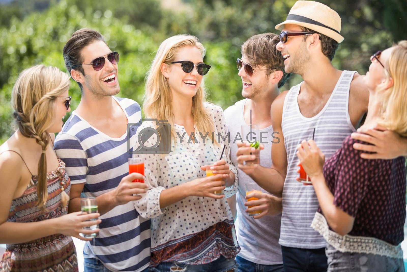 Group of happy friends having juice while enjoying together