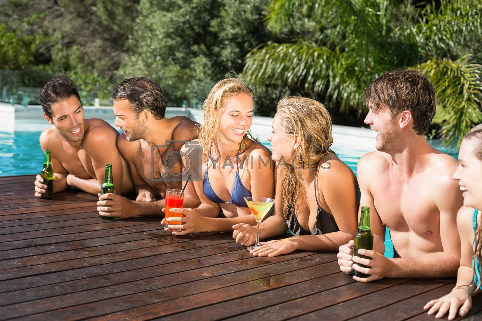 Royalty free image of Happy friends enjoying at the swimming pool by Wavebreakmedia