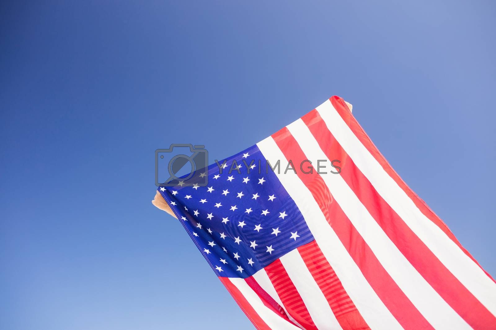 Senior man holding american flag on a sunny day
