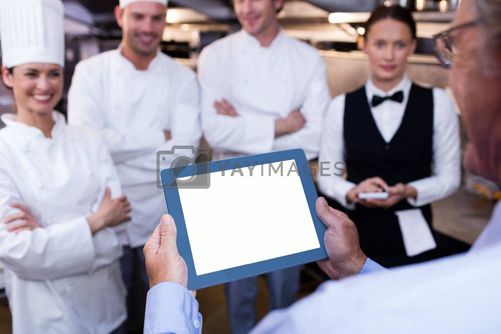 Restaurant manager briefing to his kitchen staff in the commercial kitchen