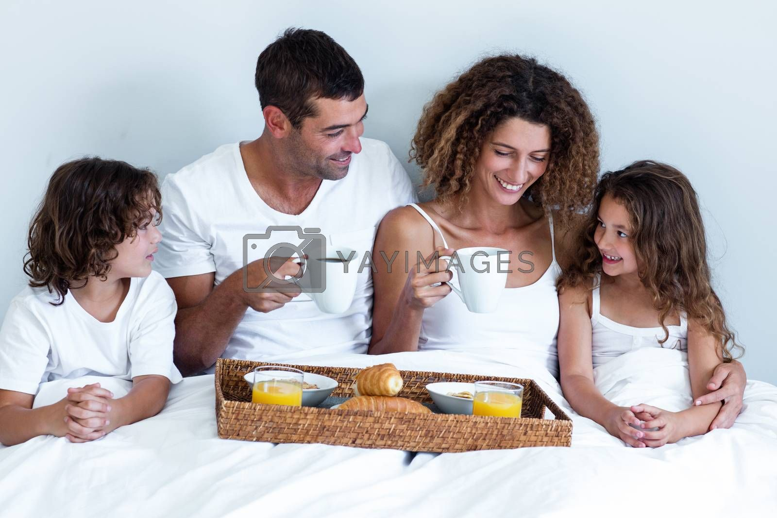 Happy family sitting with breakfast tray on bed in bedroom