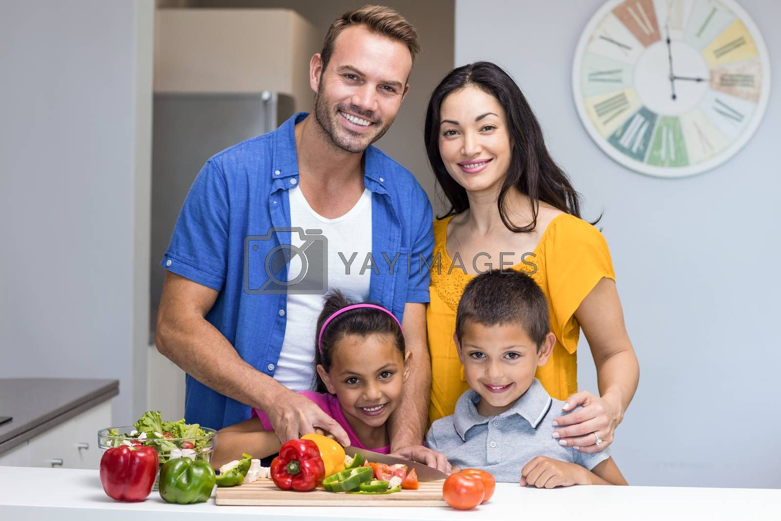 Happy family in the kitchen chopping vegetables at home