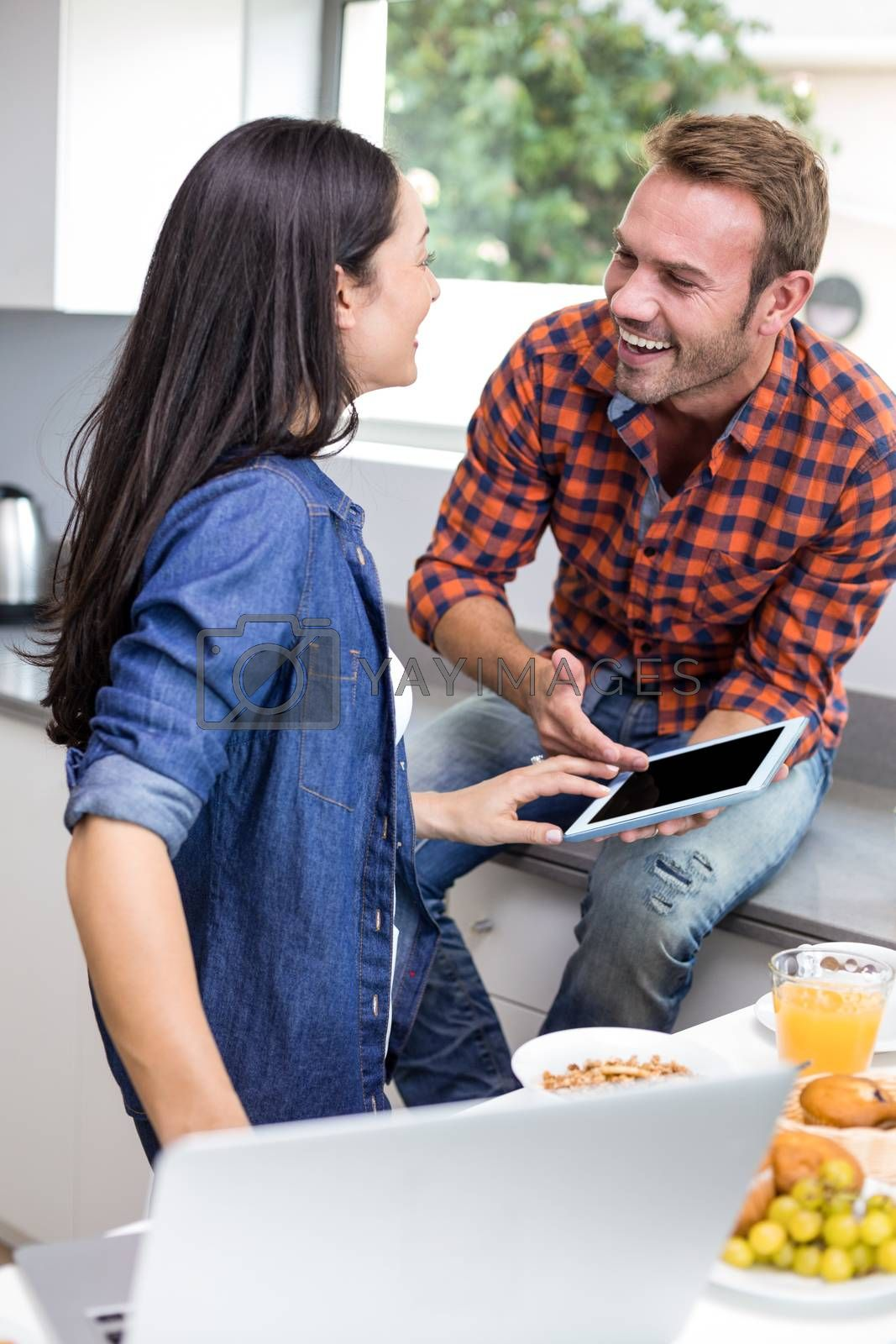 Couple interacting using laptop and digital tablet in the kitchen