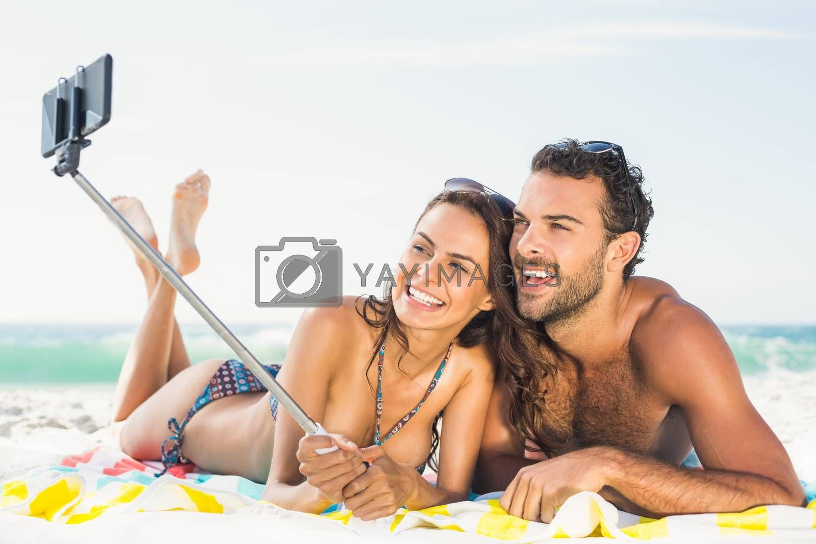 Couple taking selfie at the beach on a sunny day