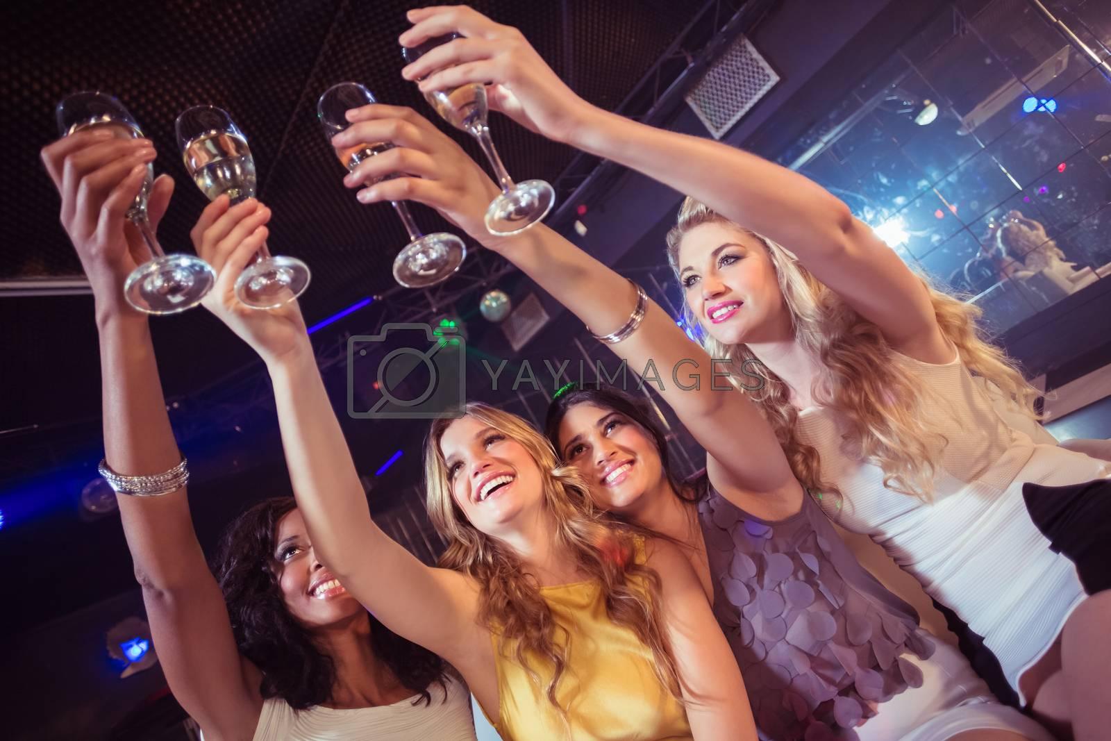 Pretty girls holding champagne glass by Wavebreakmedia