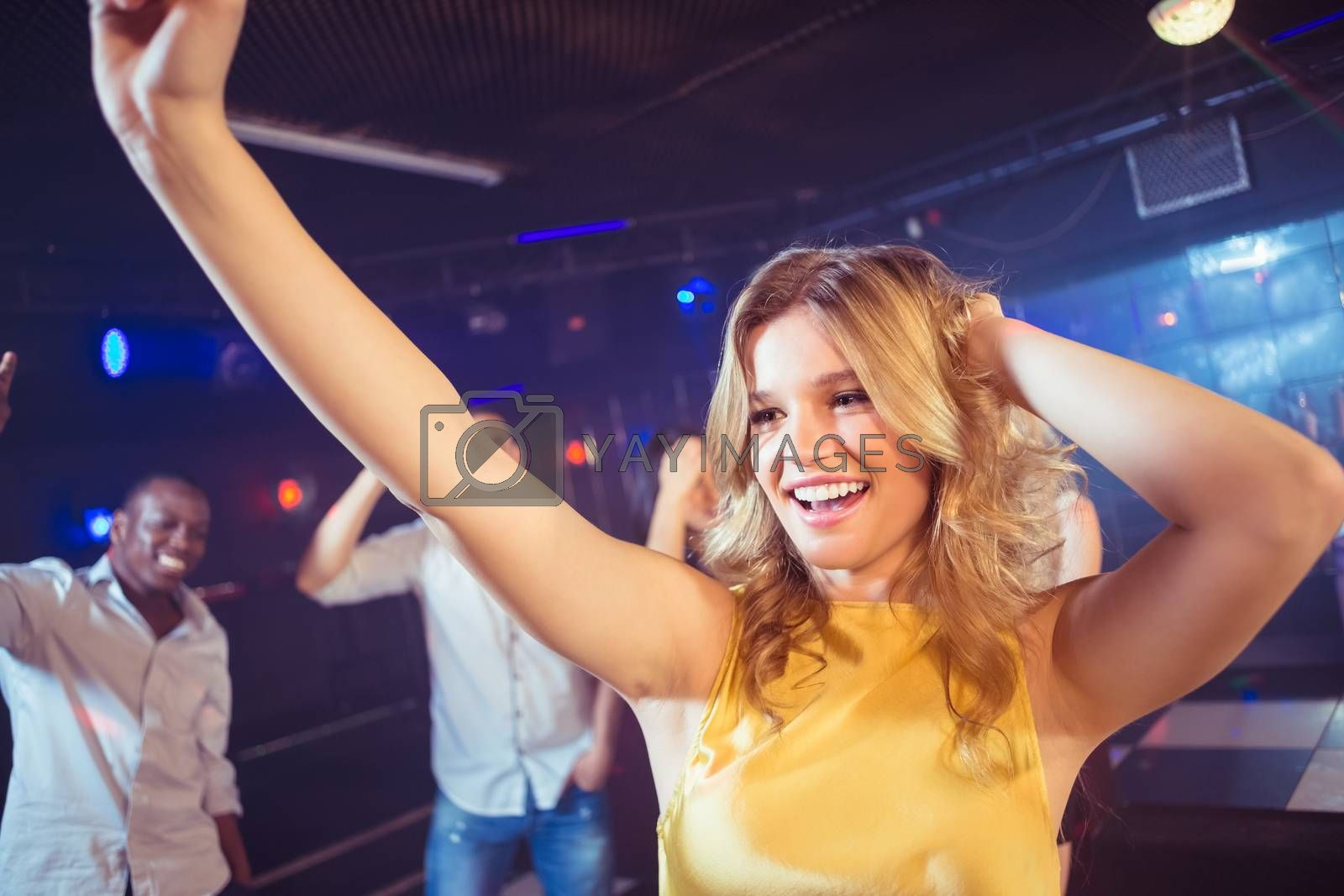 Happy friends dancing cheerfully in night club