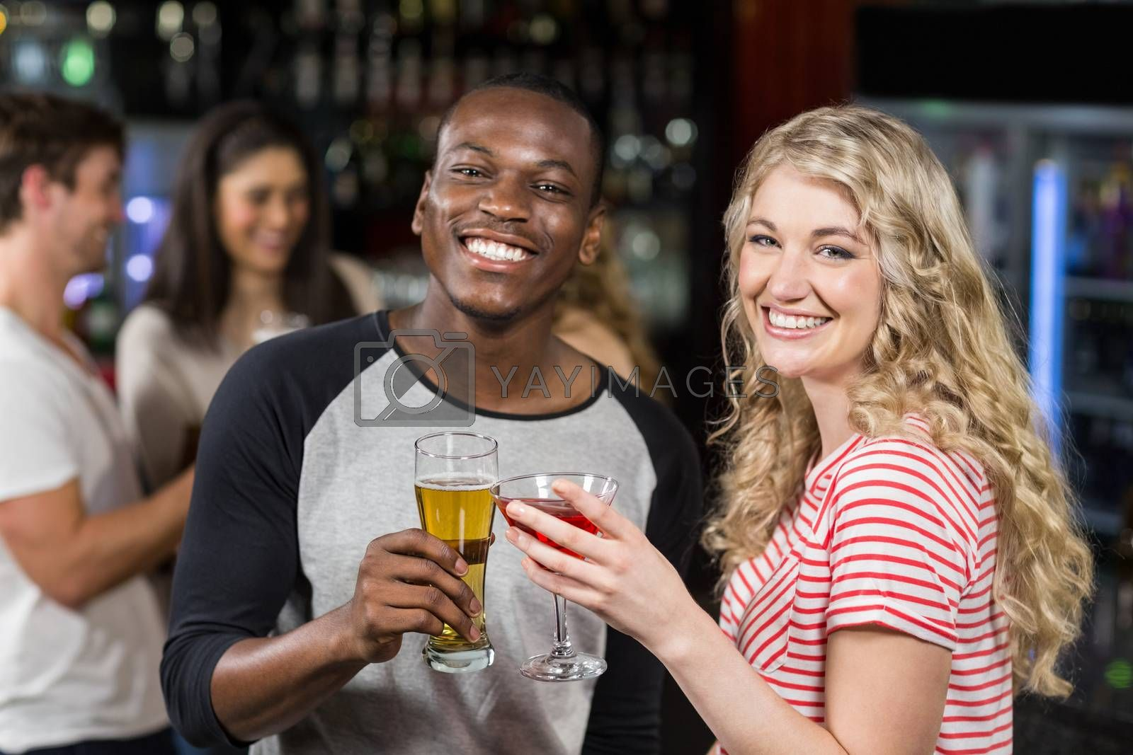 Friends toasting with cocktail and beer in a pub