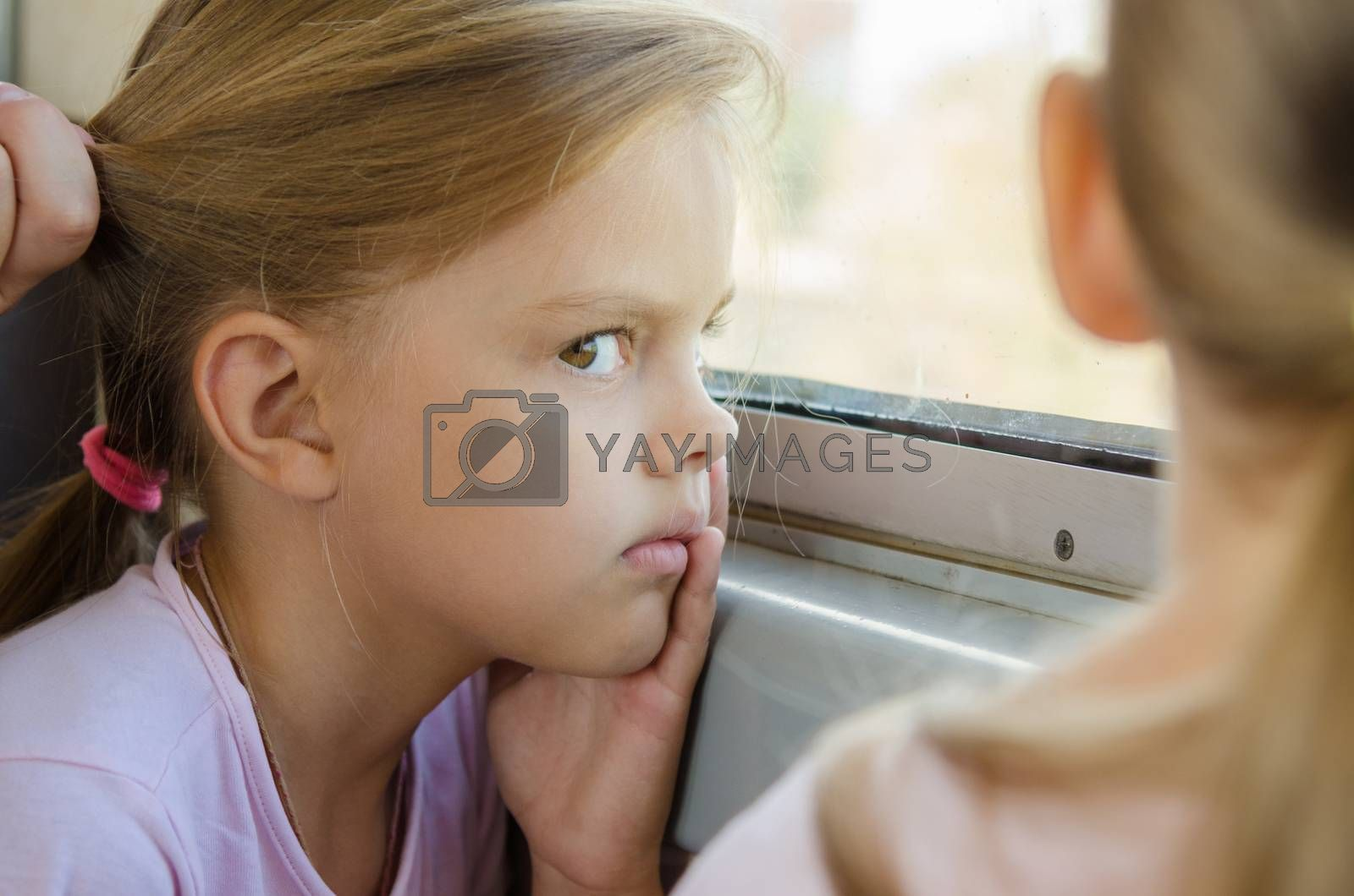 The girl glared at the other girl sitting near electric windows