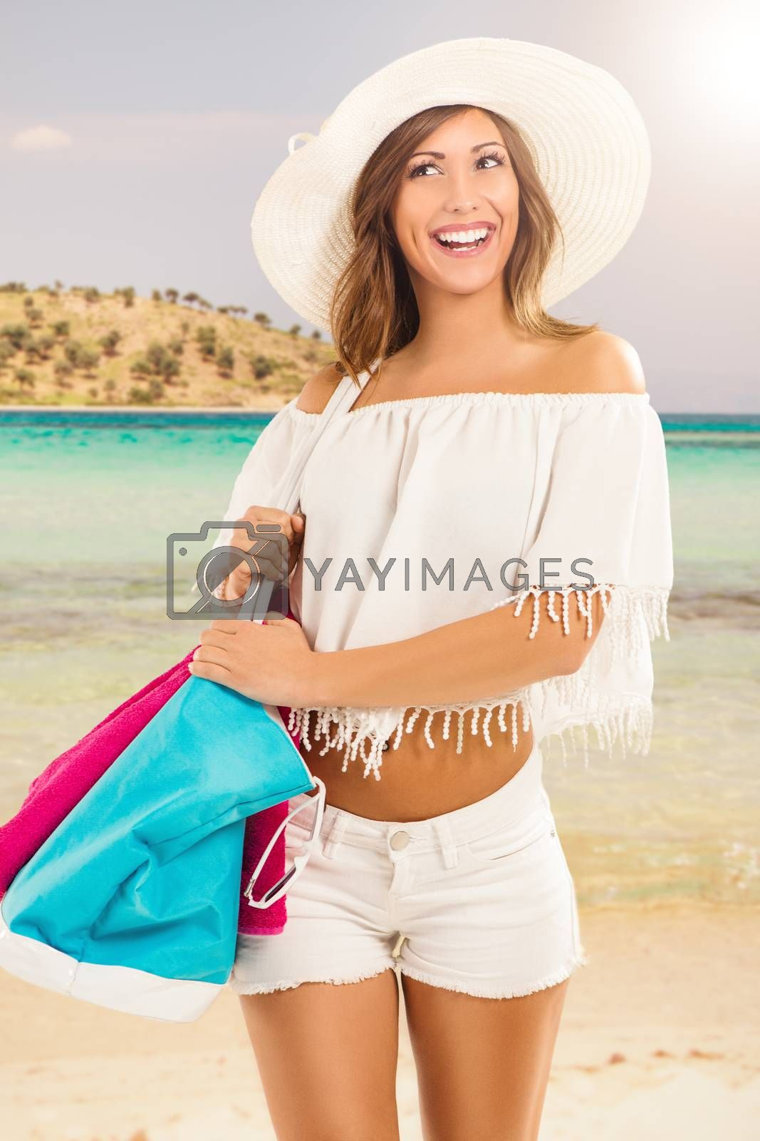 Beautiful young woman on summer vacation. She is standing with hat and holding bag and towel for beach.