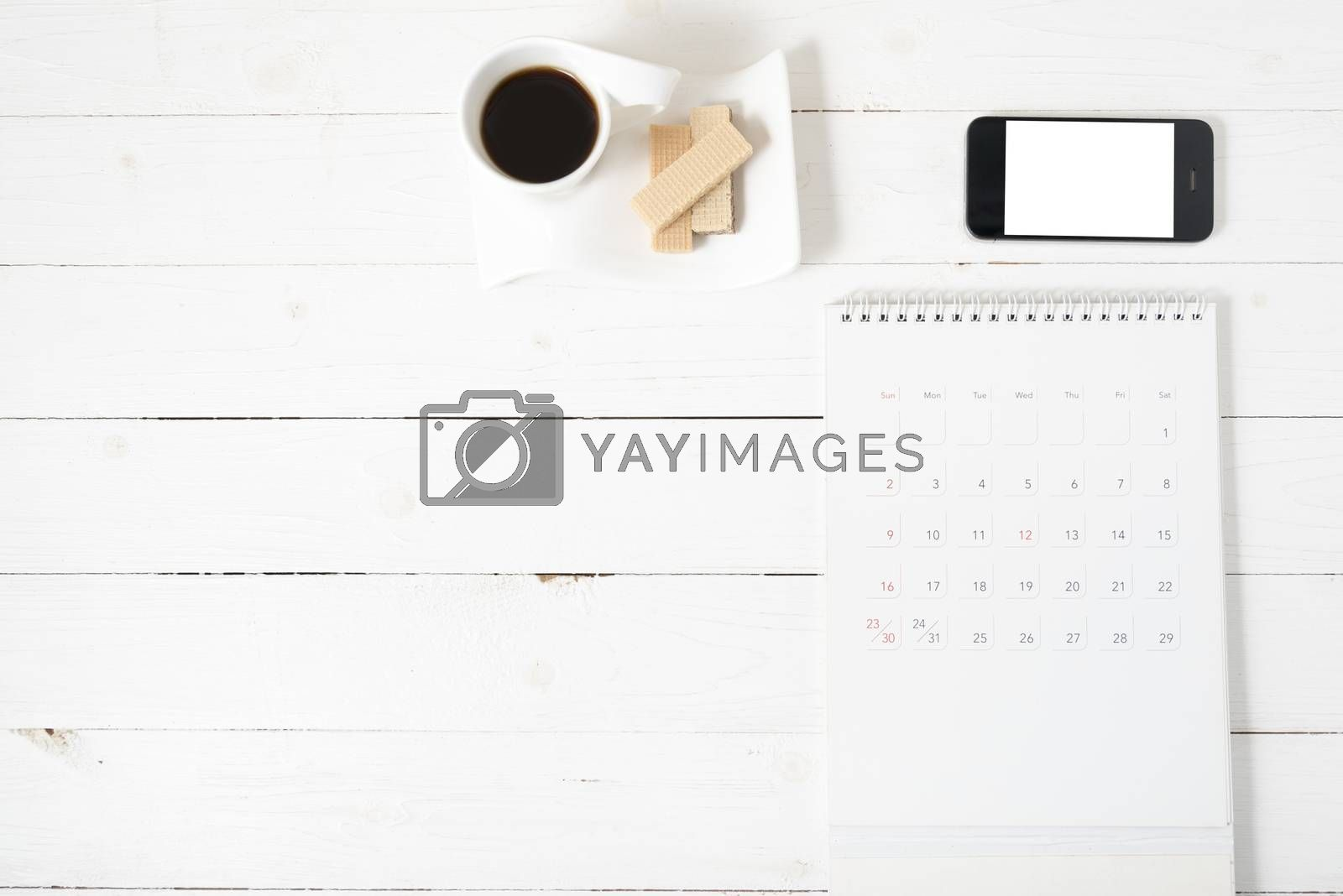 coffee cup with wafer,phone,calendar on white wood background