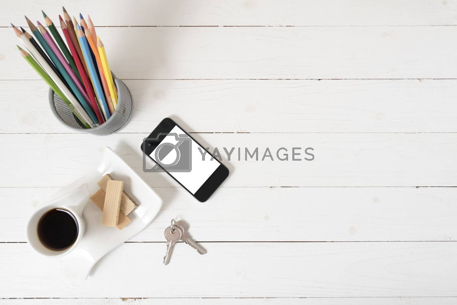 coffee cup with wafer,phone,pencil box,key on white wood background
