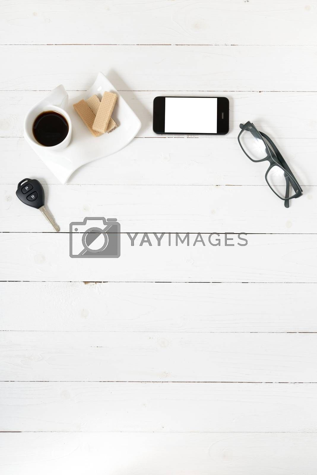 coffee cup with wafer,phone,car key,eyeglasses on white wood background