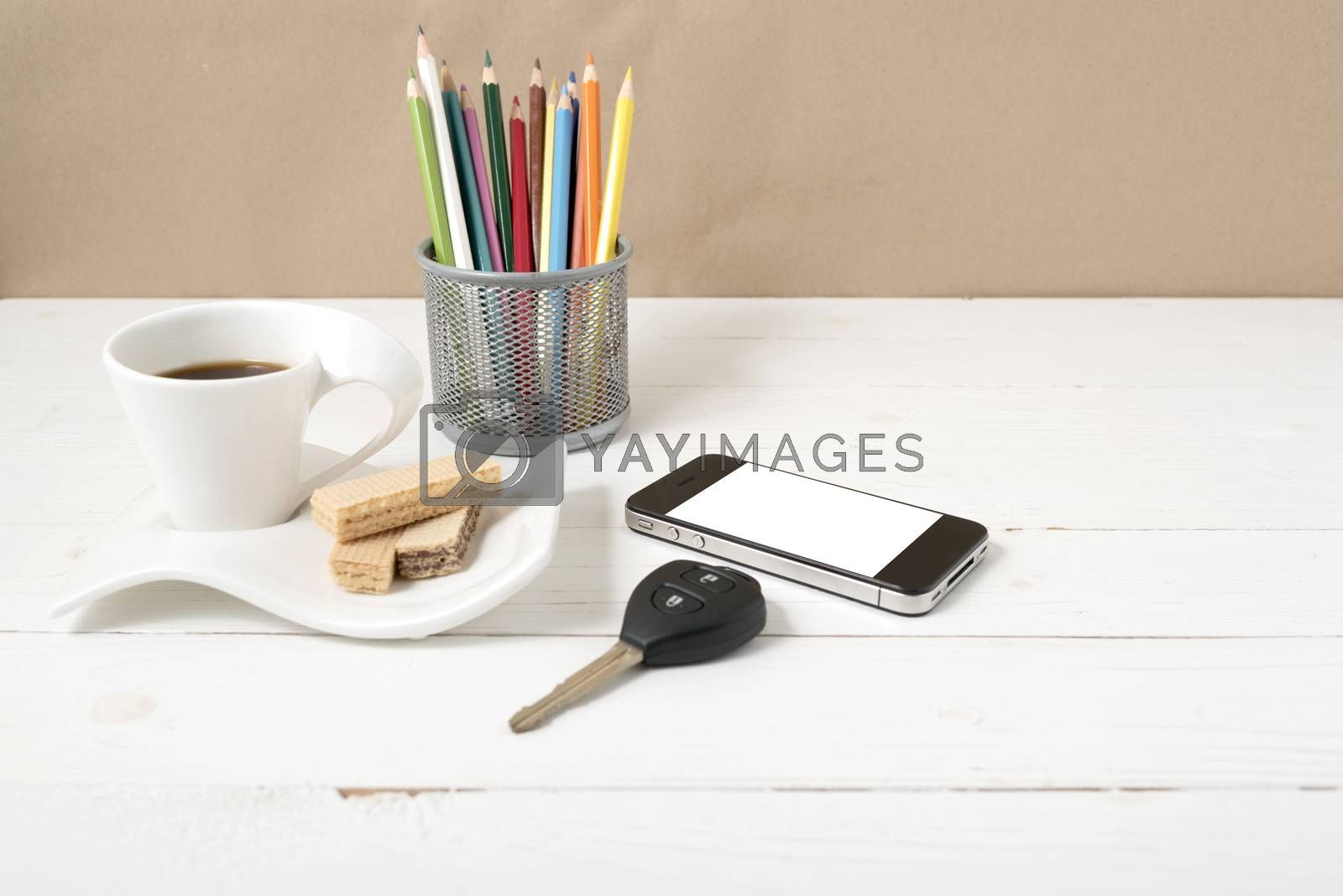coffee cup with wafer,phone,pencil box,car key on white wood background