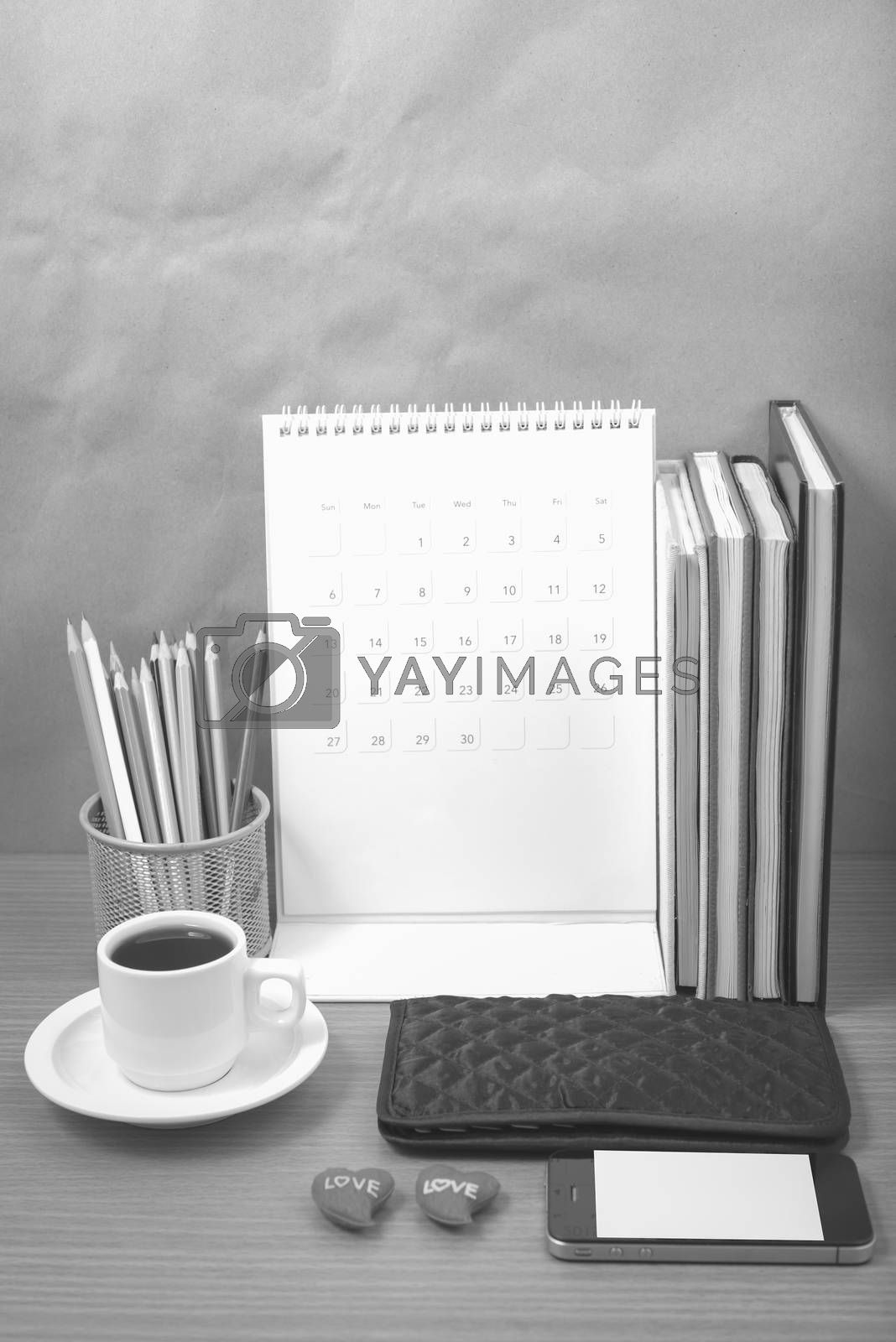 office desk : coffee with phone,wallet,calendar,heart,color pencil box,stack of book,heart on wood background black and white color