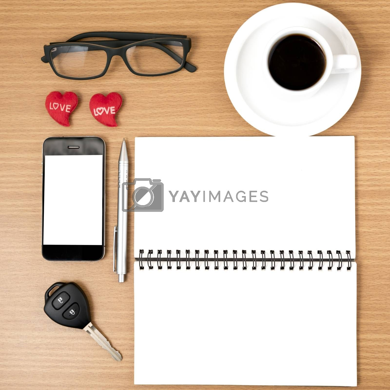 office desk : coffee and phone with car key,eyeglasses,notepad,heart on wood background