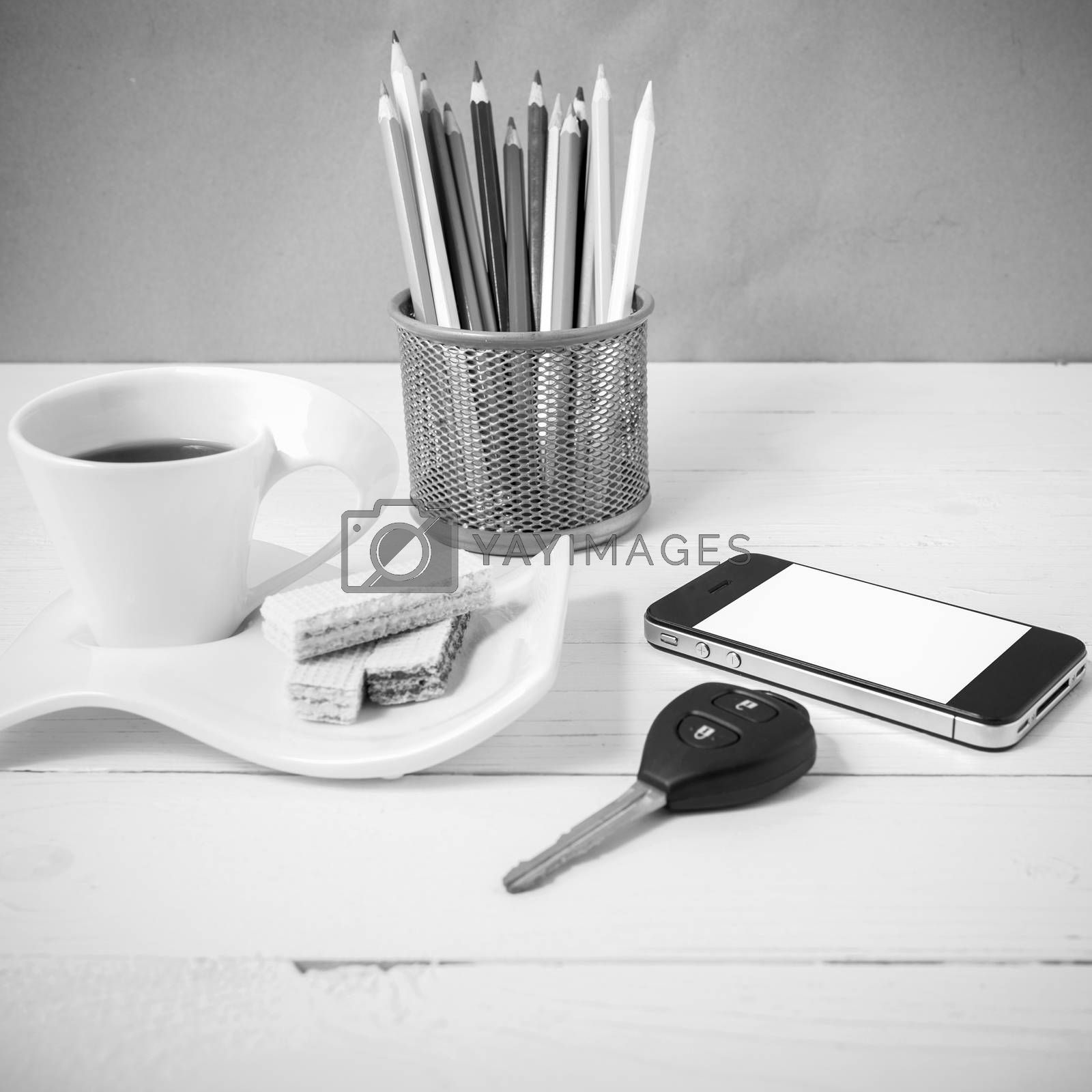 coffee cup with wafer,phone,pencil box,car key on white wood background black and white color