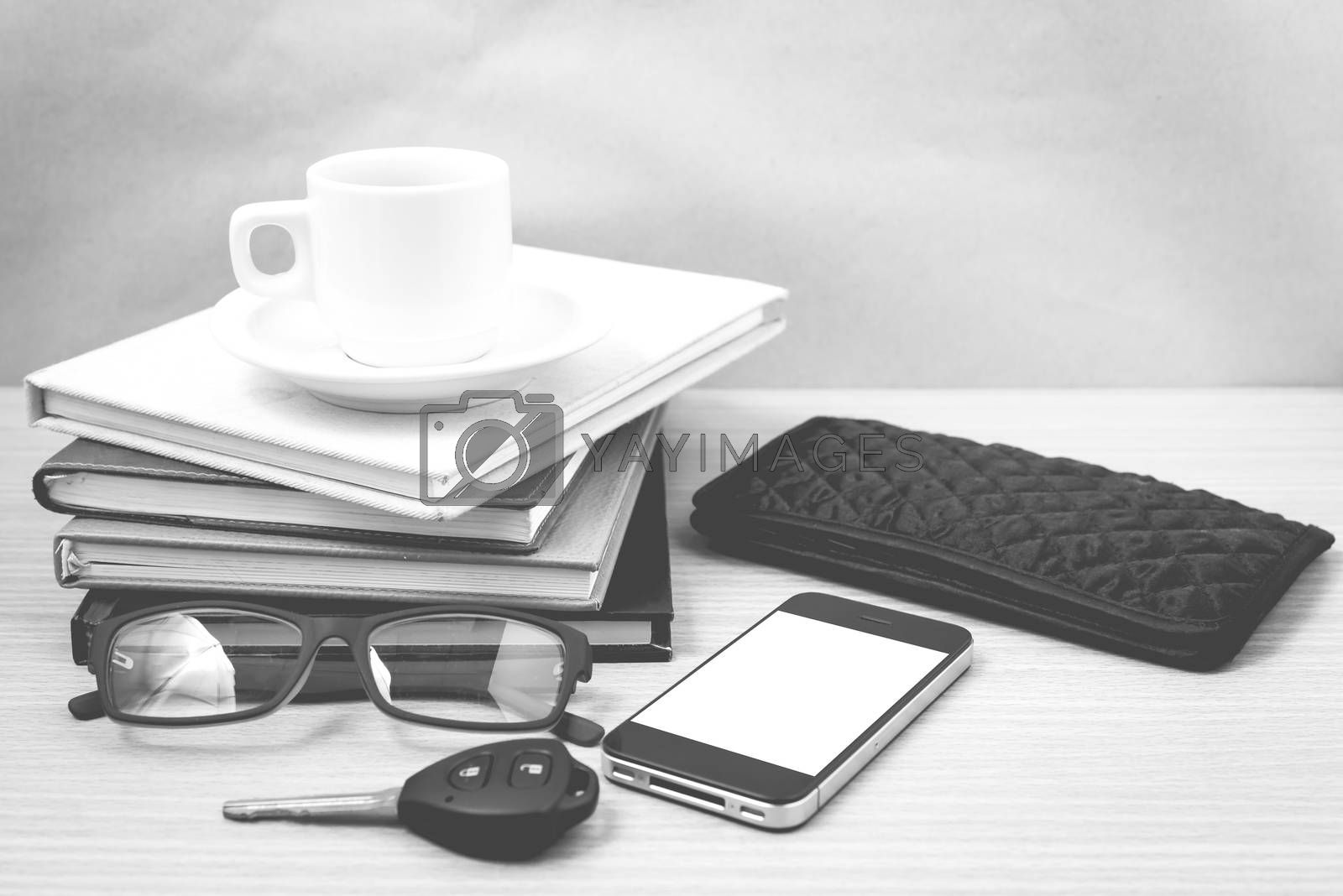 coffee and phone with stack of book,car key,eyeglasses and wallet on wood background black and white color