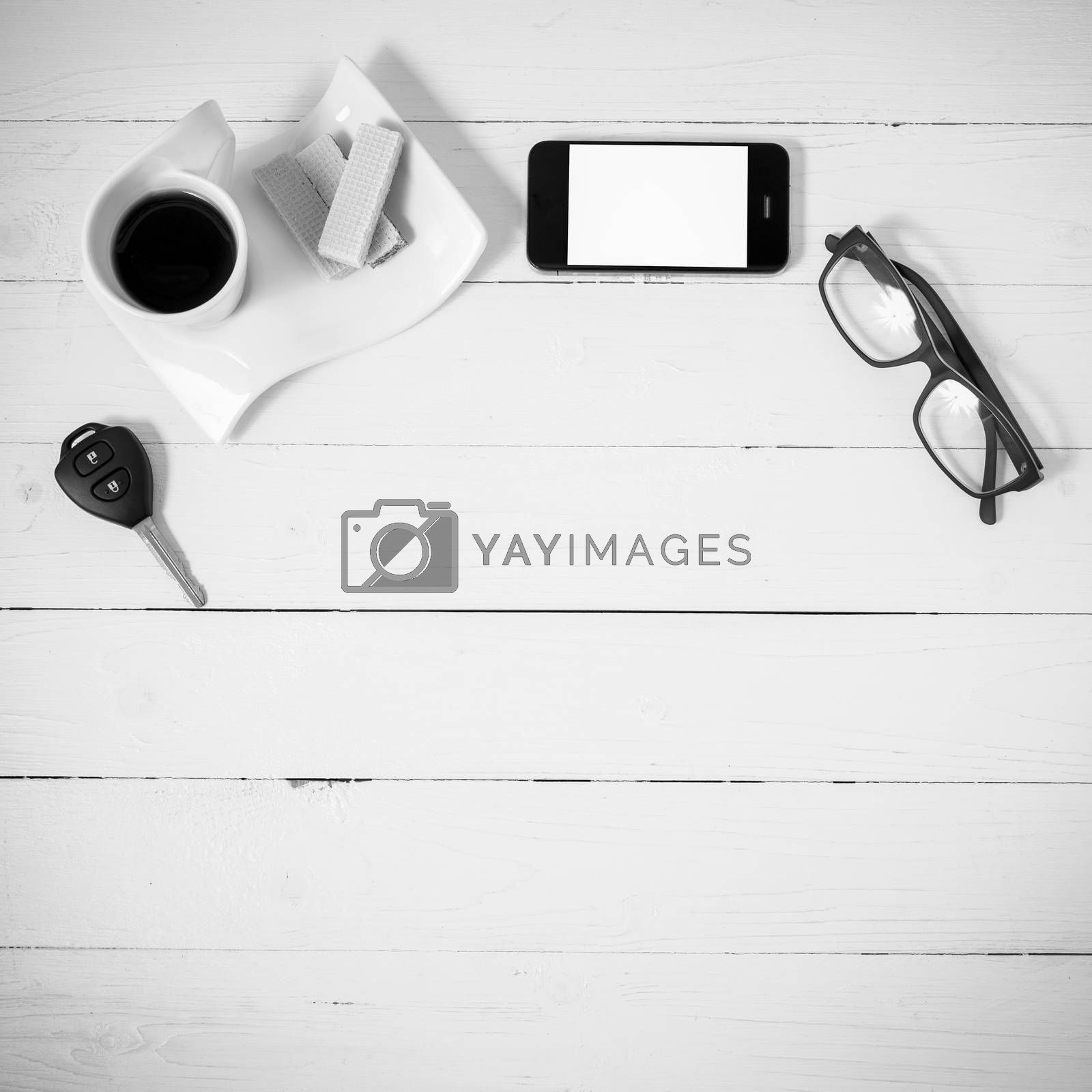 Royalty free image of coffee cup with wafer,phone,car key,eyeglasses black and white c by ammza12