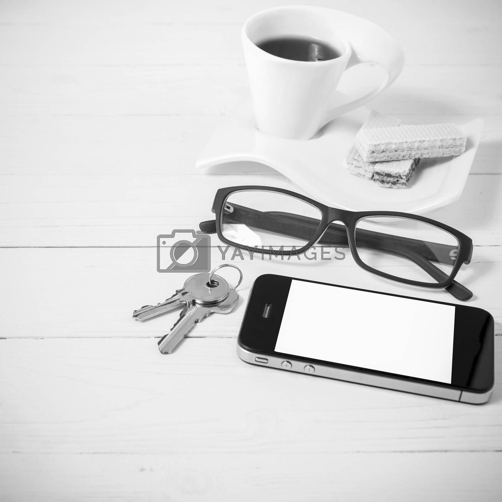 coffee cup with wafer,phone,key,eyeglasses on white wood background black and white color