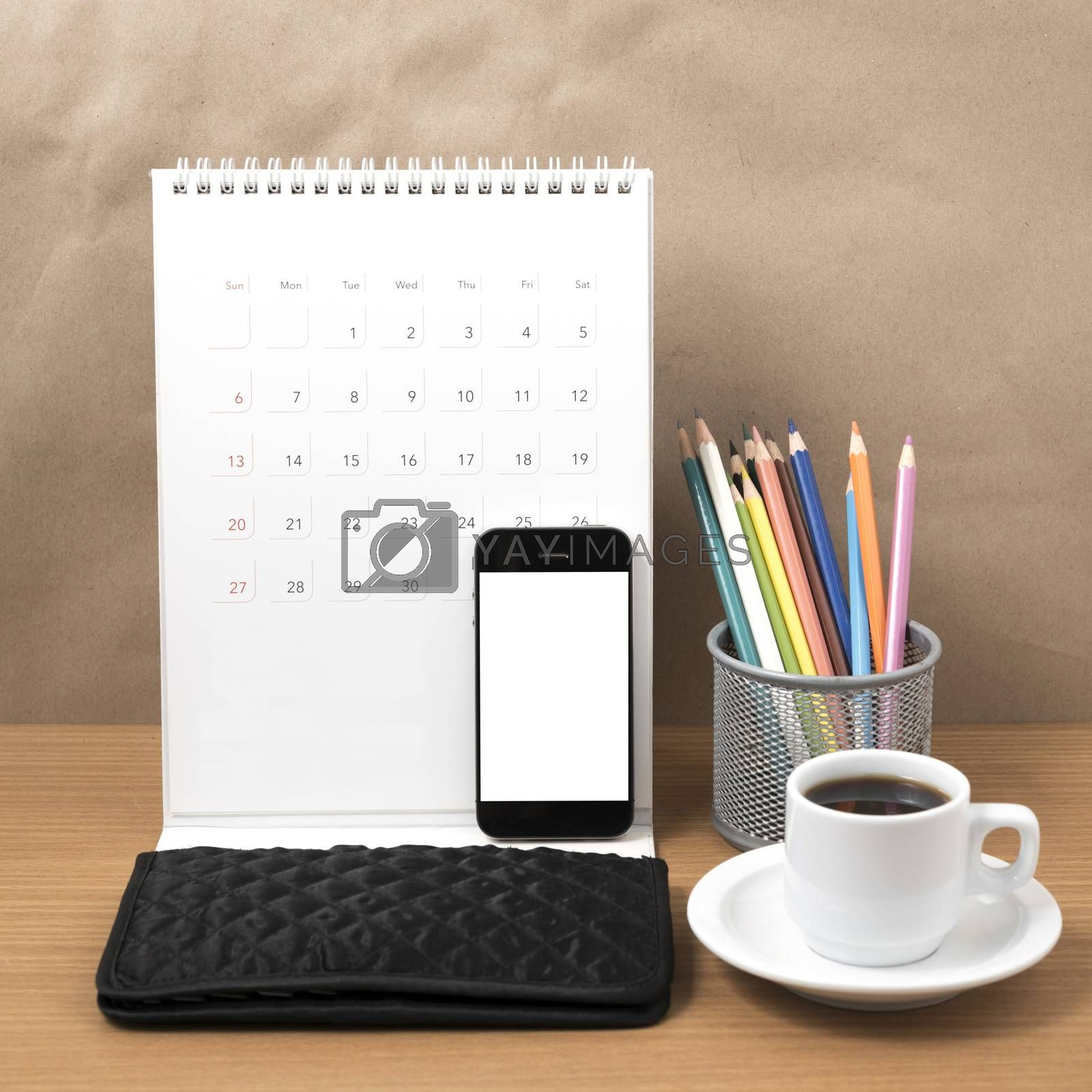 office desk : coffee with phone,calendar,wallet,color pencil on wood background