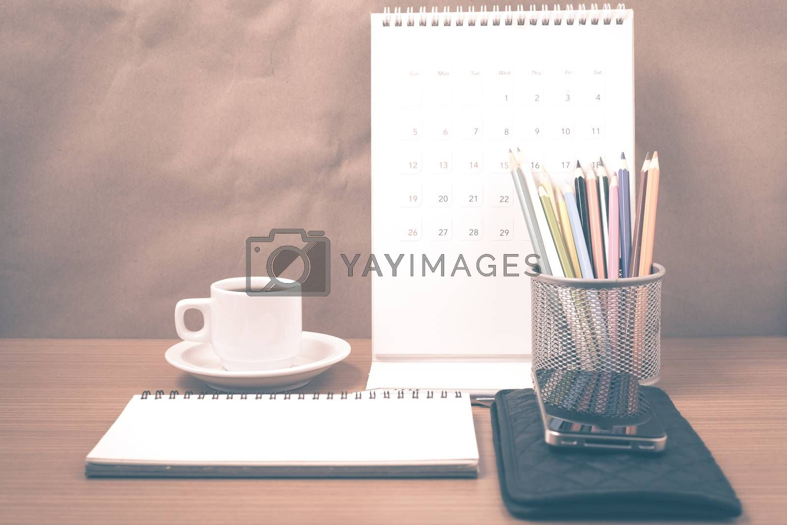 office desk : coffee with phone,wallet,calendar,color pencil box,notepad on wood background vintage style