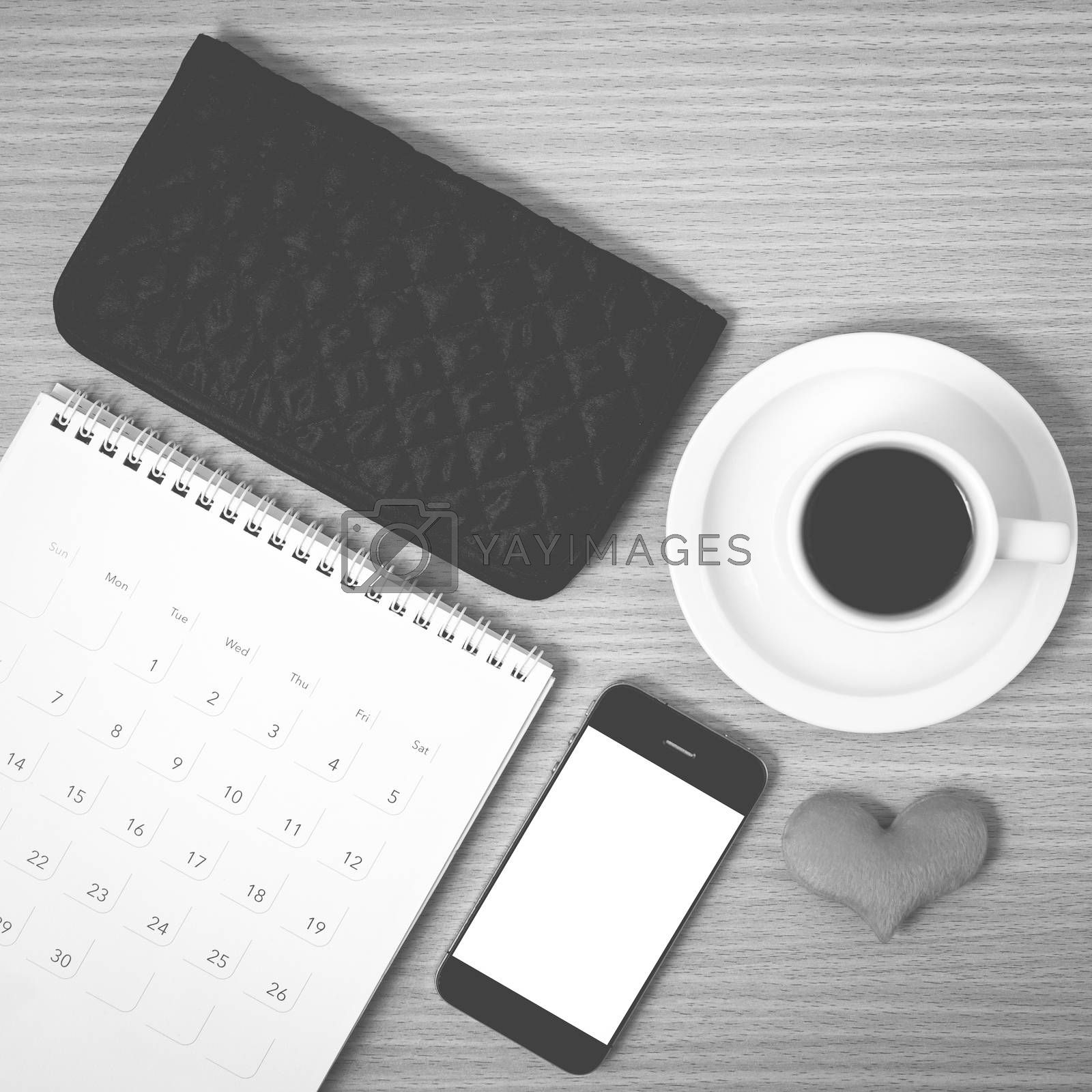 office desk : coffee with phone,wallet,calendar,heart on wood background black and white color