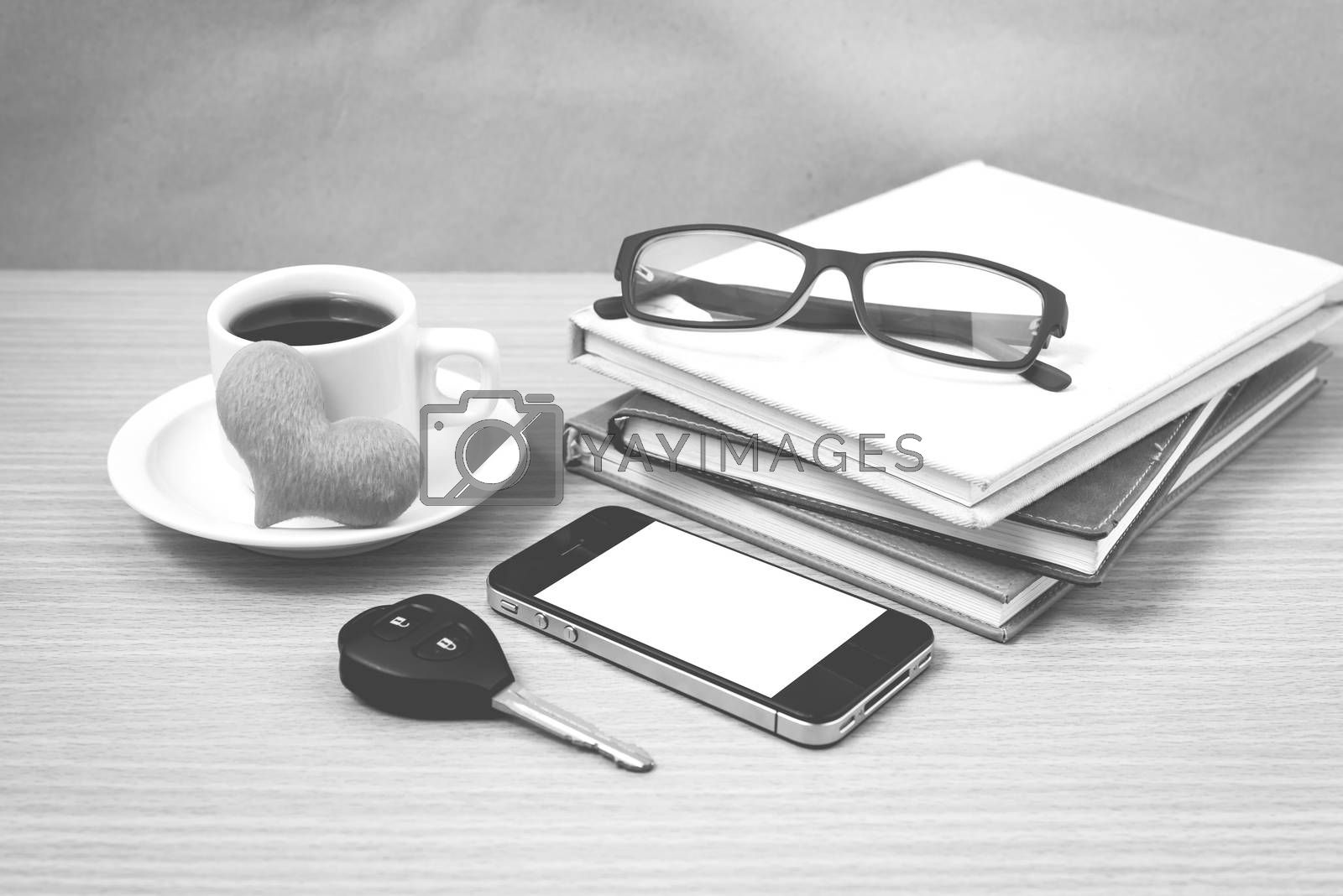office desk : coffee and phone with car key,eyeglasses,stack of book,heart black and white color