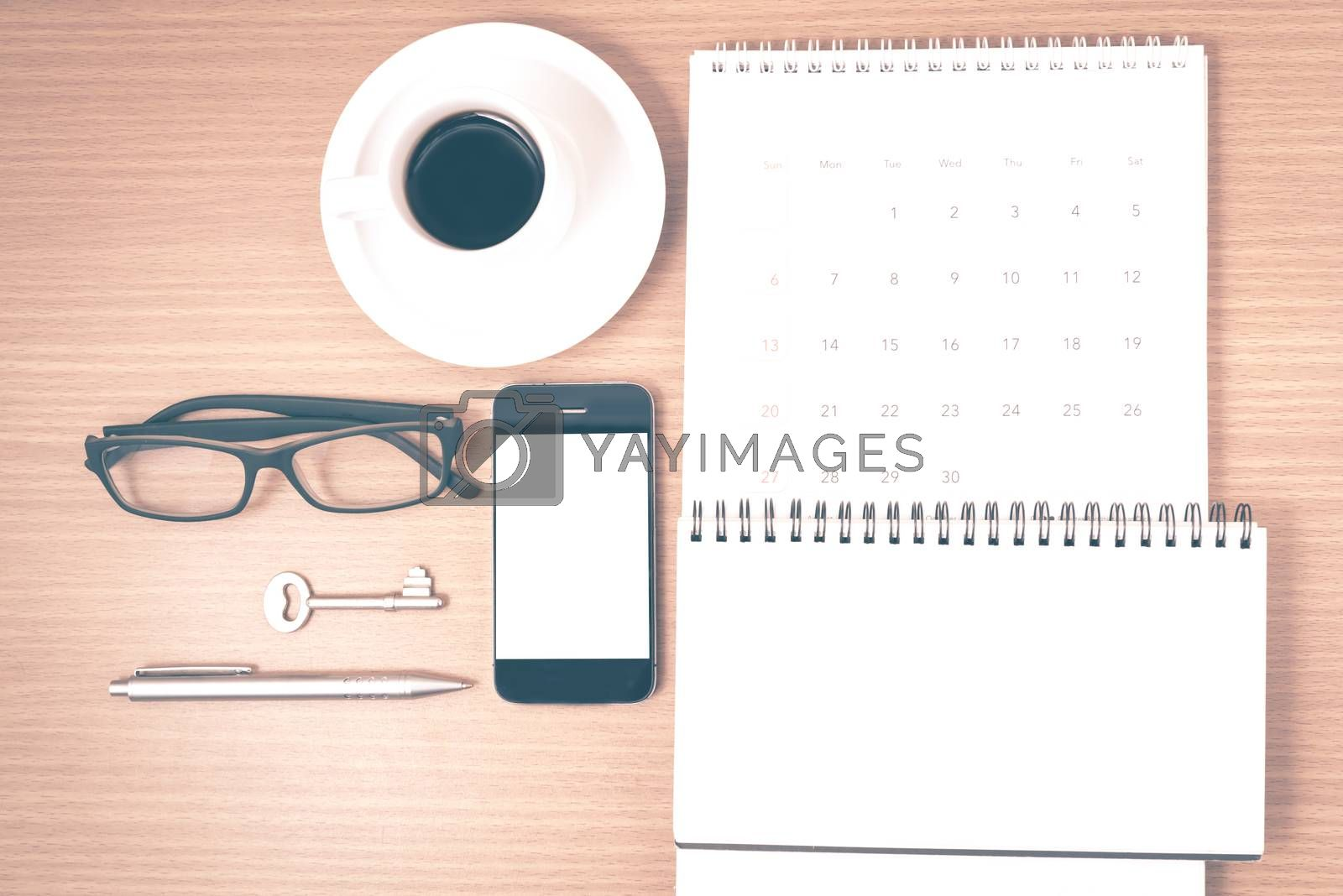coffee and phone with key,eyeglasses,notepad,calendar on wood table background vintage style