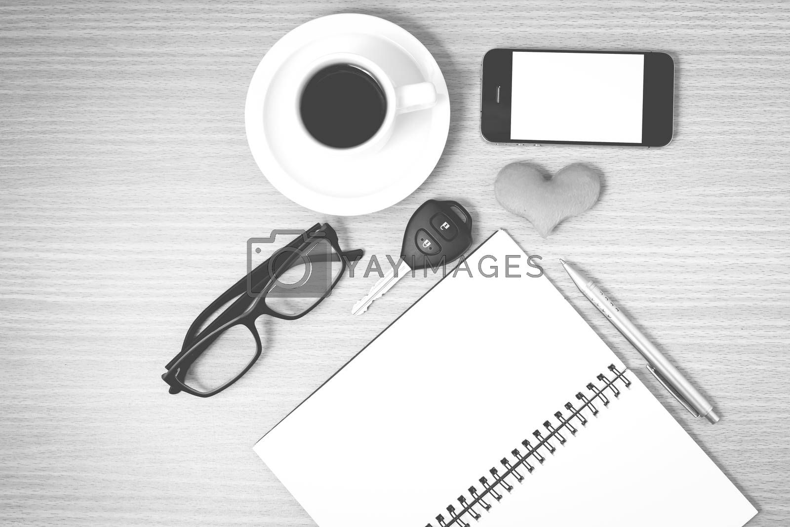 office desk : coffee and phone with car key,eyeglasses,notepad,heart on wood background black and white color