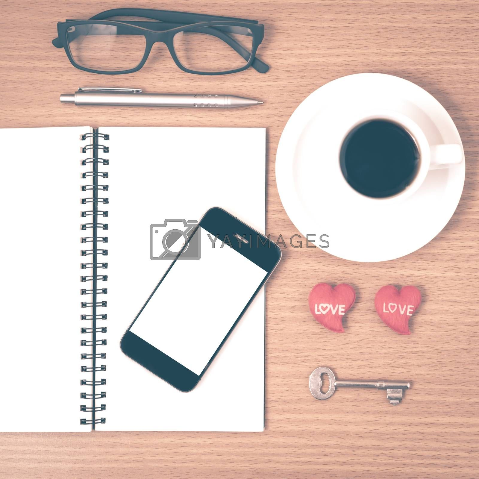 office desk : coffee and phone with key,eyeglasses,notepad,heart on wood background vintage style
