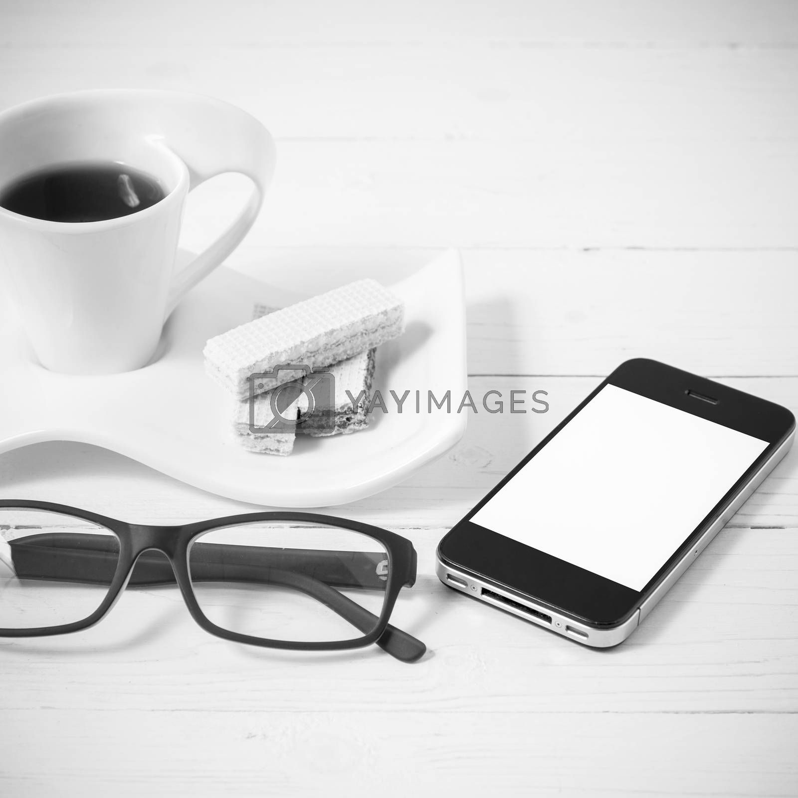 coffee cup with wafer,phone,eyeglasses on white wood background black and white color
