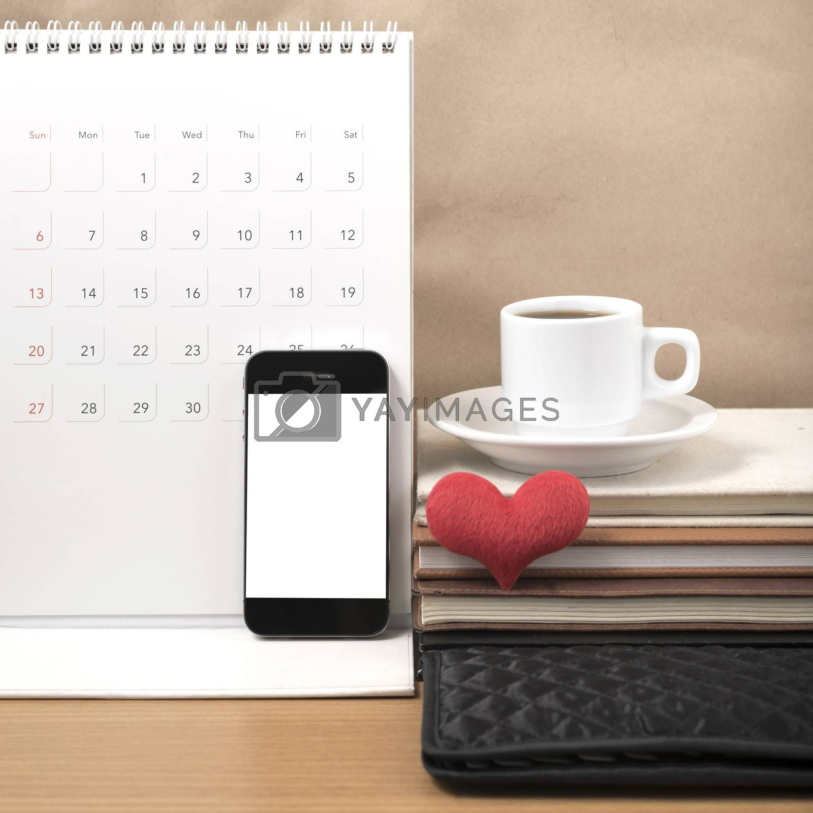 office desk : coffee with phone,wallet,calendar,heart,stack of book on wood background