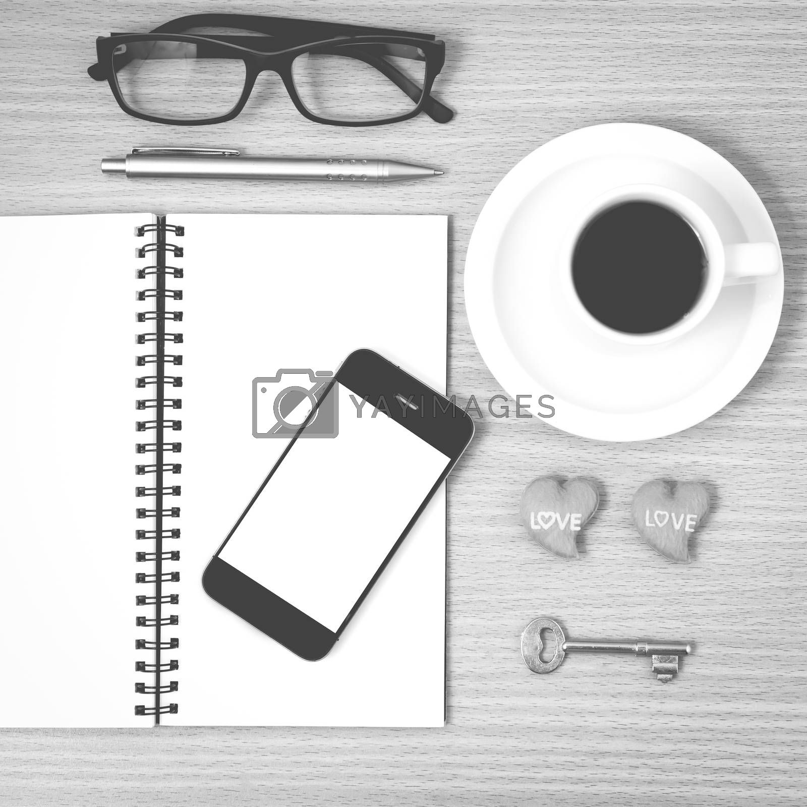 office desk : coffee and phone with key,eyeglasses,notepad,heart on wood background black and white color