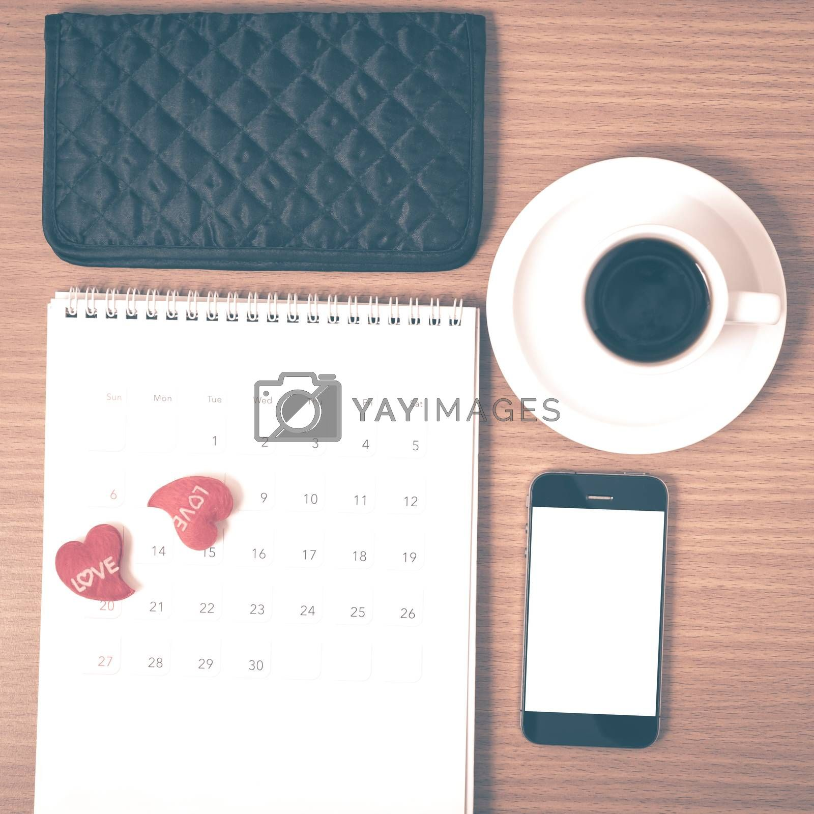 office desk : coffee with phone,calendar,wallet,heart on wood background vintage style