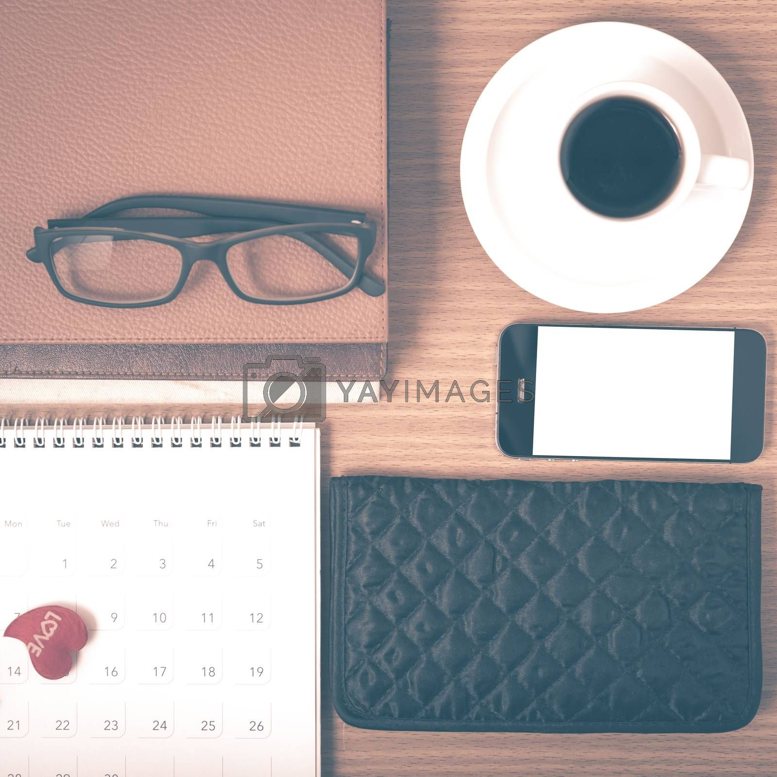 office desk : coffee with phone,stack of book,eyeglasses,wallet,calendar,heart on wood background vintage style