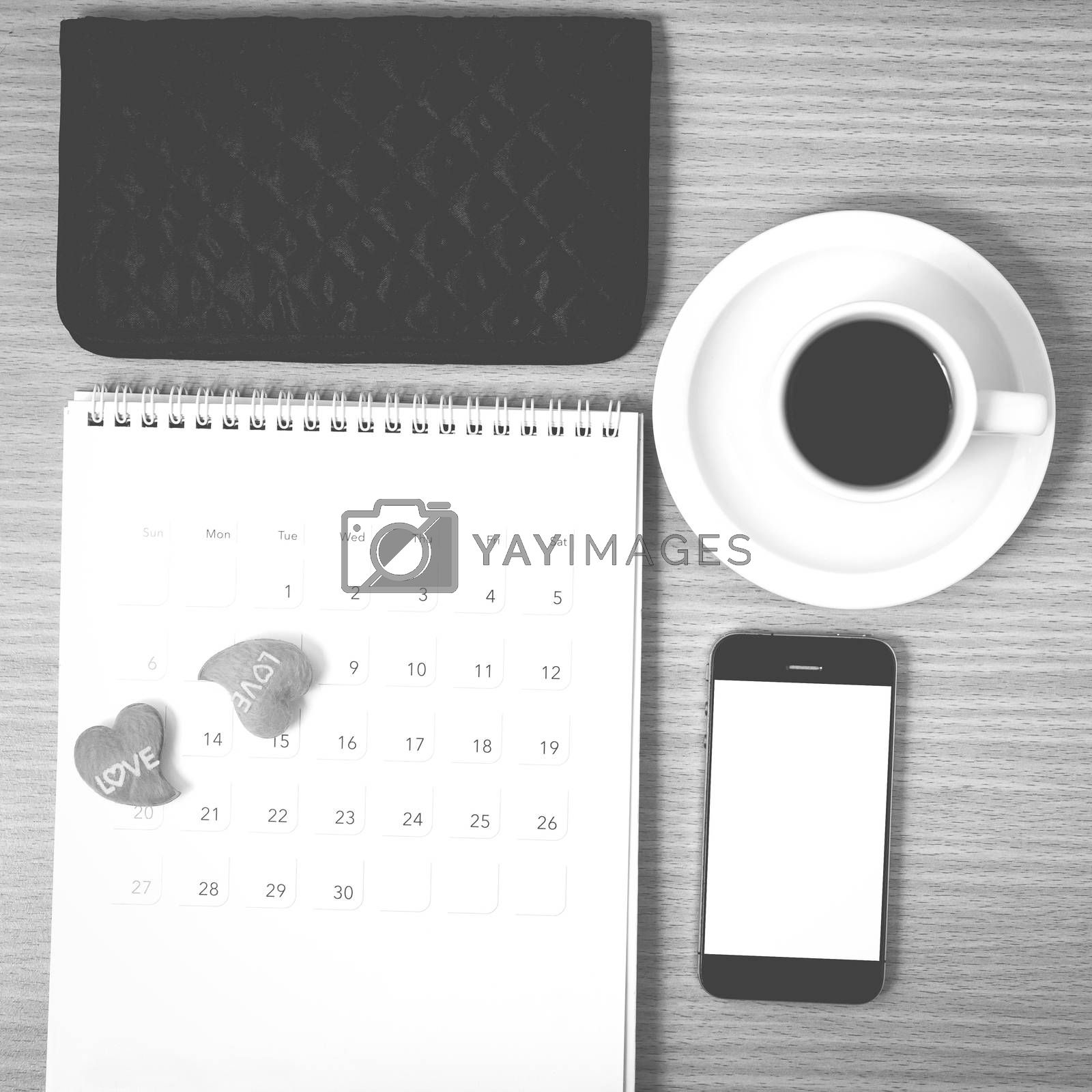 office desk : coffee with phone,calendar,wallet,heart on wood background black and white color