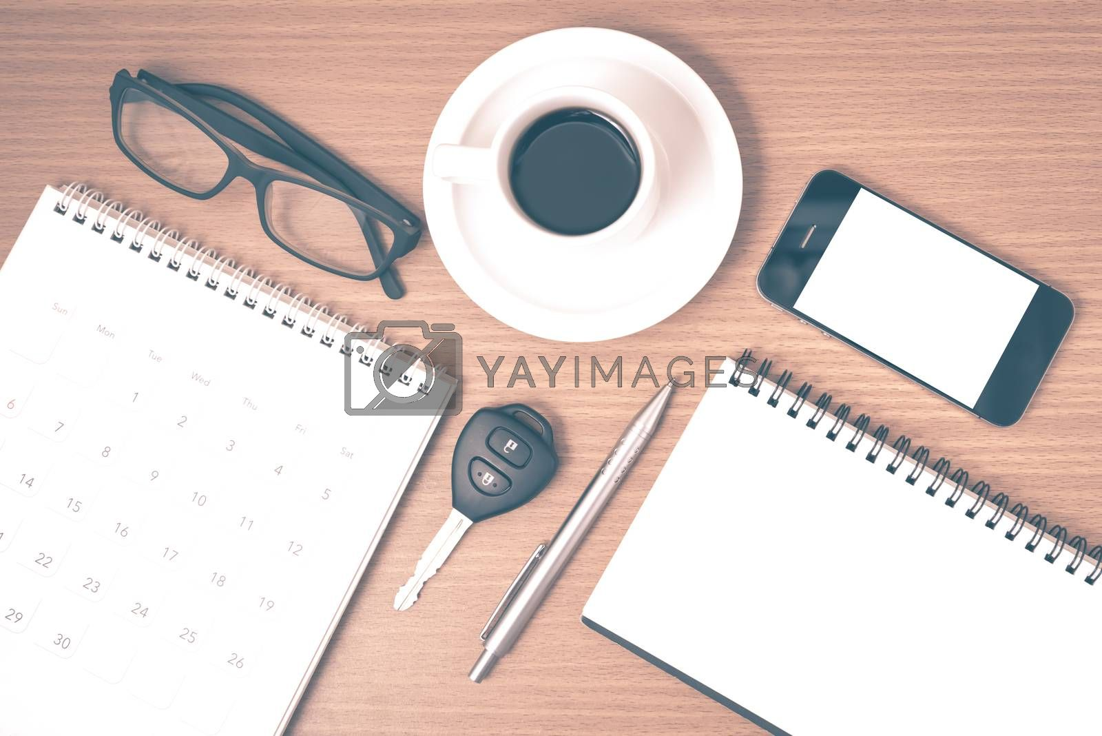 coffee and phone with car key,eyeglasses,notepad,calendar on wood background vintage style