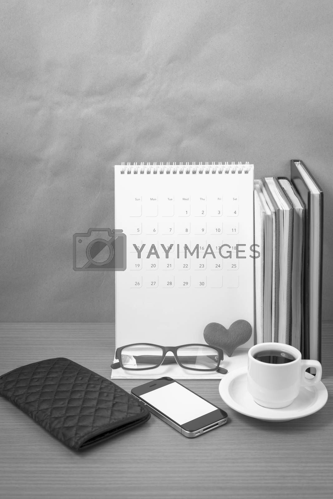 desktop : coffee with phone,stack of book,wallet,heart,eyeglasses,calendar on wood background black and white color
