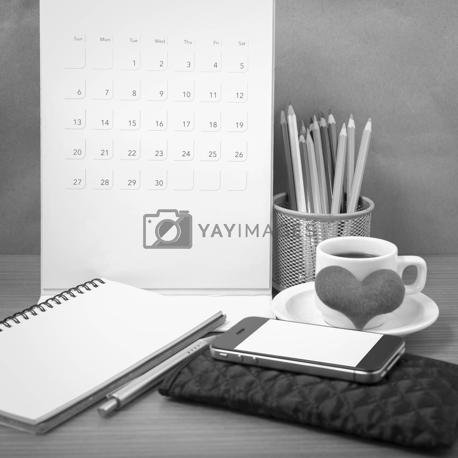 office desk : coffee with phone,wallet,calendar,heart,color pencil box,notepad,heart on wood background black and white color