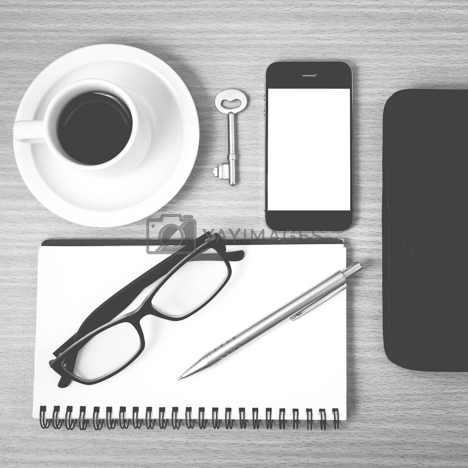 coffee and phone with notepad,key,eyeglasses and wallet on wood table background black and white color