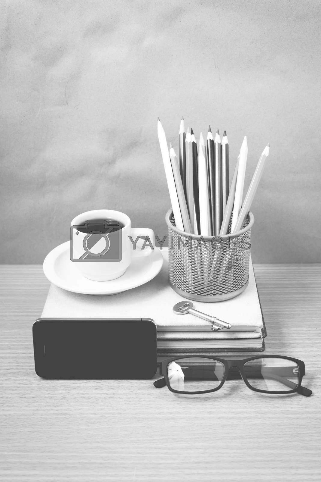 office desk : coffee and phone with key,eyeglasses,stack of book,pencil box black and white color