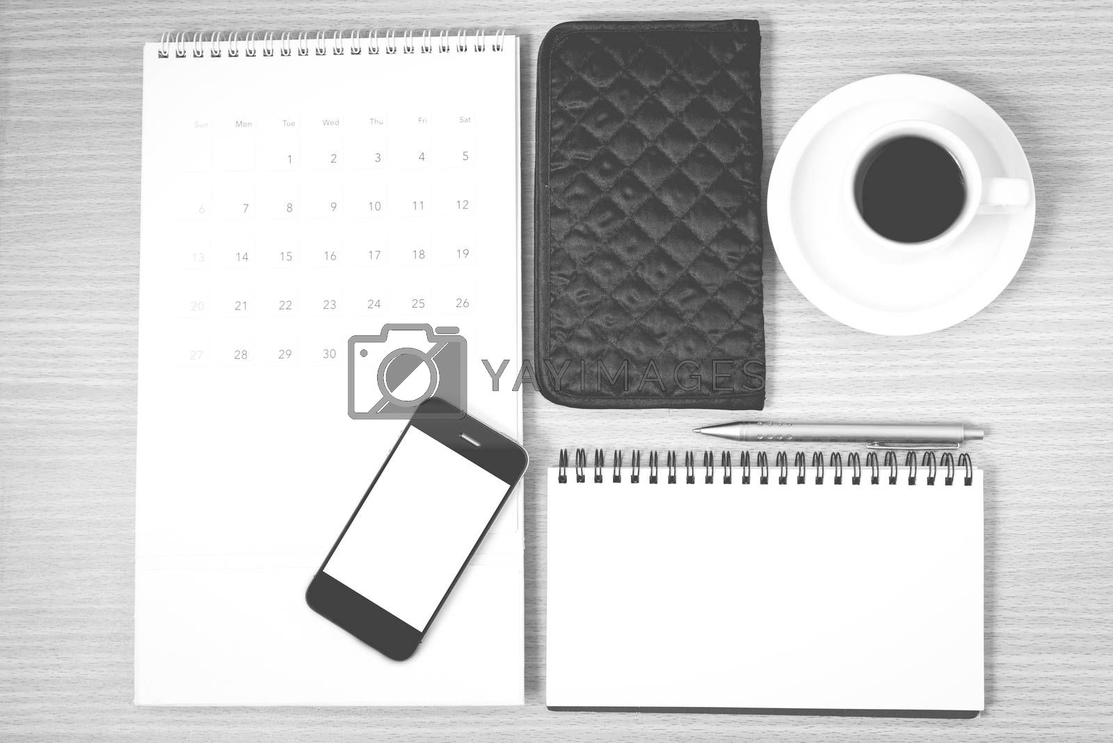desktop : coffee with phone,notepad,wallet,calendar on wood background black and white color
