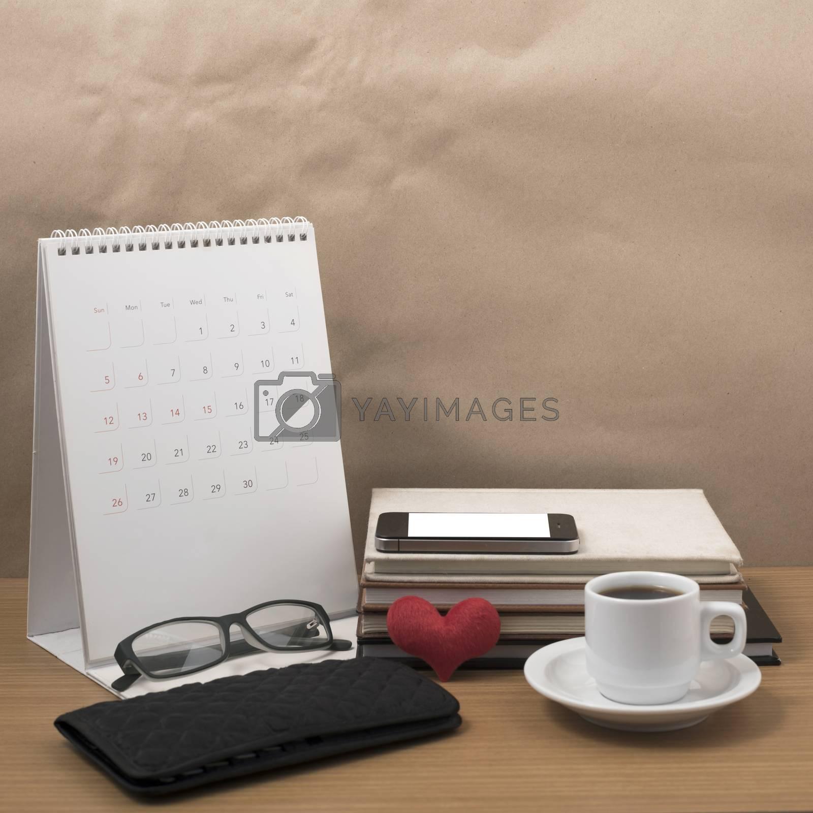 desktop : coffee with phone,stack of book,wallet,heart,eyeglasses,calendar on wood background