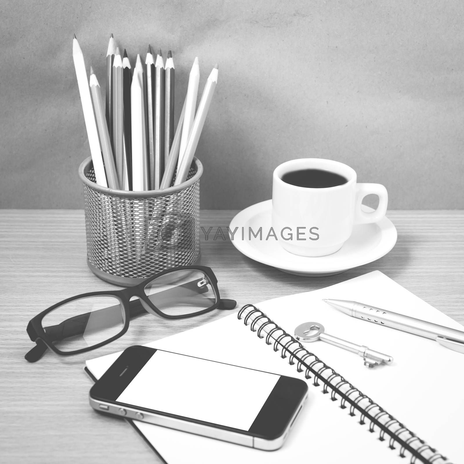 office desk : coffee and phone with key,eyeglasses,notepad,pencil box black and white color