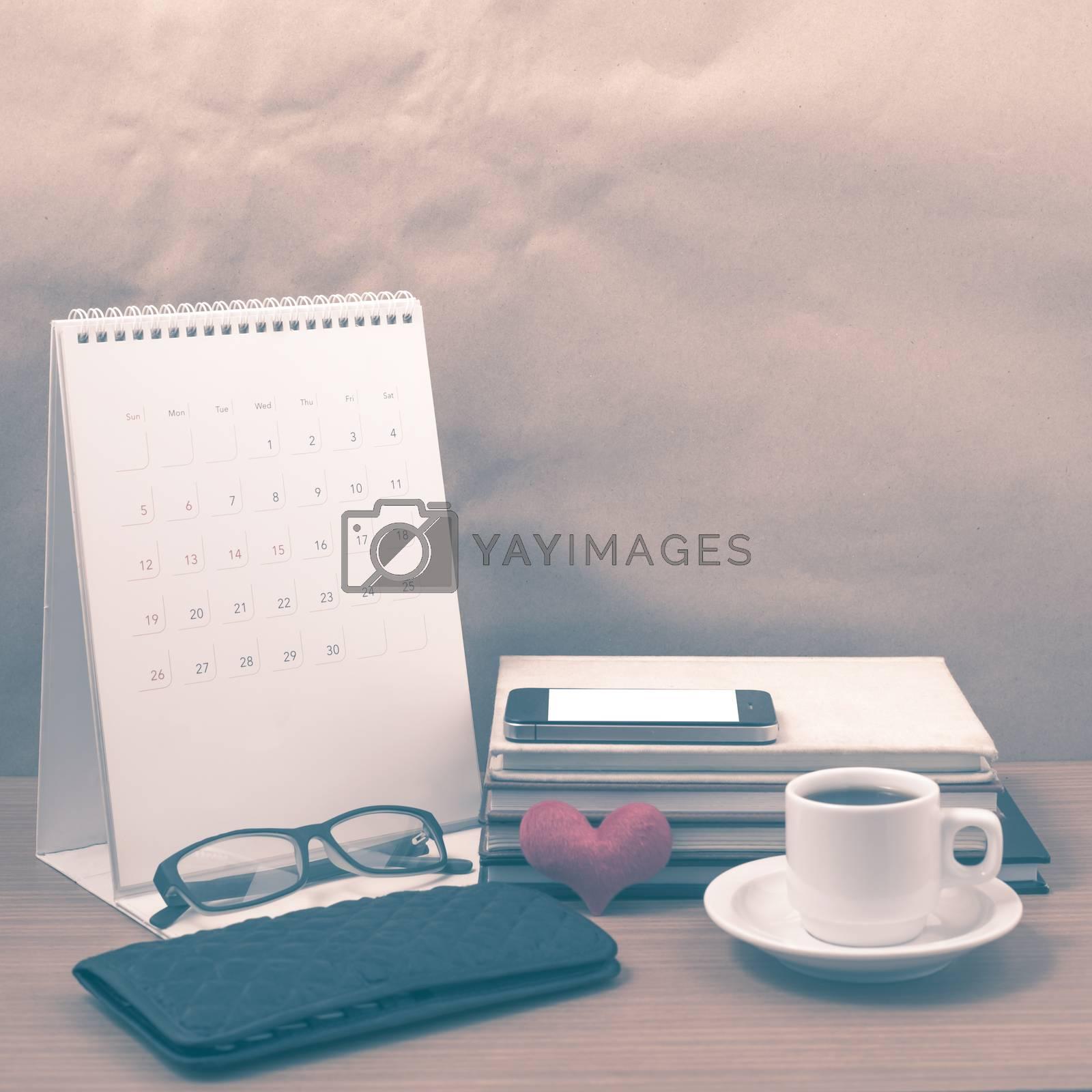 desktop : coffee with phone,stack of book,wallet,heart,eyeglasses,calendar on wood background vintage style